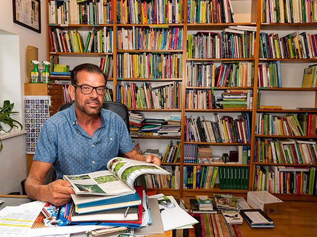 Biogärtner Karl Ploberger beim Bücher-Schmökern (Bild: Cadmos/Christoph Böhler)